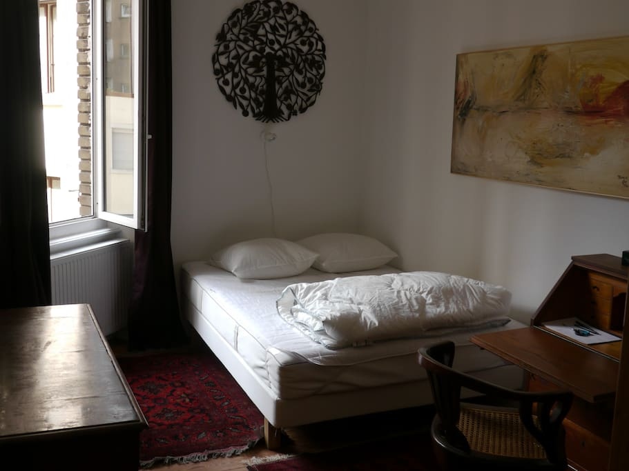 the room on offer , a double bed, wardrobe, drawer, nicely decorated with metal art form Haiti and an oil painting from Niger and an oil painting from Vietnam. A wardrobe ,  chest with 3 drawers, writing desk, calm view to interior court yard.