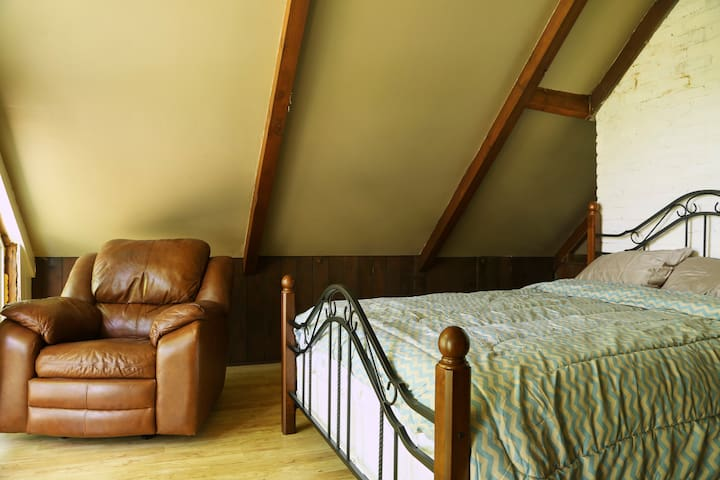 The loft with a queen bed and rocker recliner