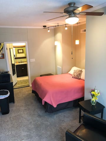 Cozy sleeping area in this queen sized bed, directly across from a TV mounted on the wall. Beneath the TV is a cabinet with the microwave, all the dishes, glasses, silverware, plates & bowls you'll need, as well as 4 drawers for additional storage of your things.