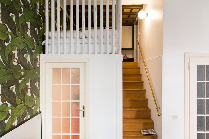 Large comfortable steps to the mezzanine with a built in wardrobe and a small but very particular bathroom.
