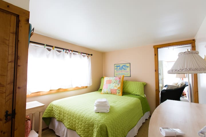 Bedroom with queen bed & dresser, flooded with natural light and restful beach theme