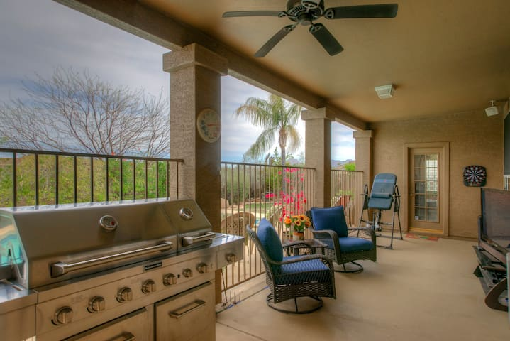 Covered veranda with gas grill and flat-screen TV viewing area.