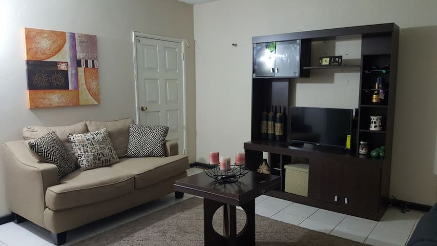 Spacious living room with two couches and an entertainment center. The smart TV is alexa enabled and carries Netflix (among many other streaming apps that you can access with your subscription).