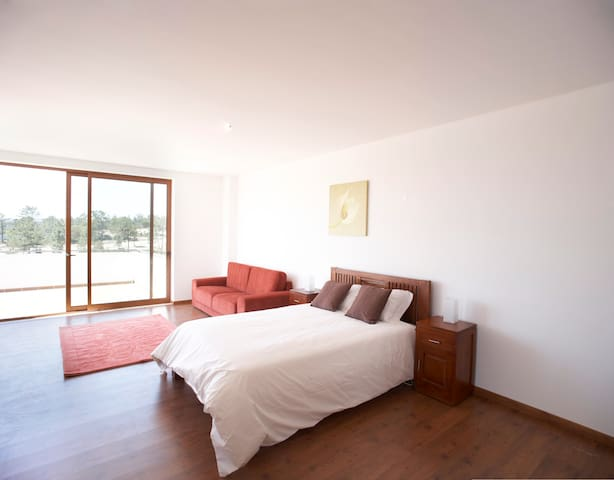 Enormous master bedroom with king-size bed, sofa area and sliding doors onto large balcony
