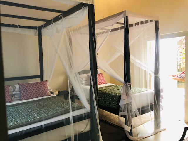 Third bedroom with a double queen bed, a single bed and another single bed in an adjoining linked smaller room.