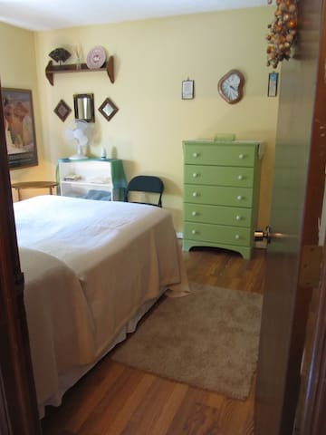 There's a dresser and bookshelf holds washcloths, towels and a fan.