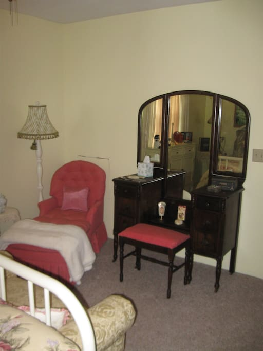 Chaise lounge chair next to vanity.