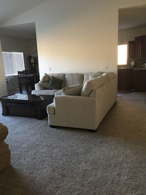 Open Living Room w/gas fireplace- large window flows into the kitchen and dining areas.