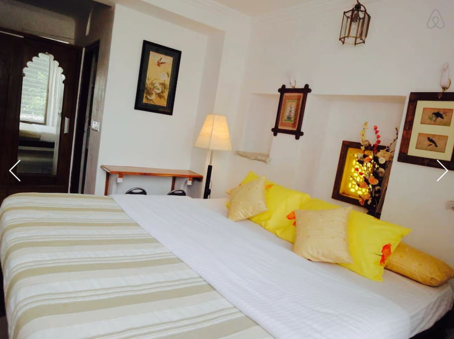 Cozy bright bedroom decorated with beautiful handmade paintings & inbuilt wooden wardrobe..