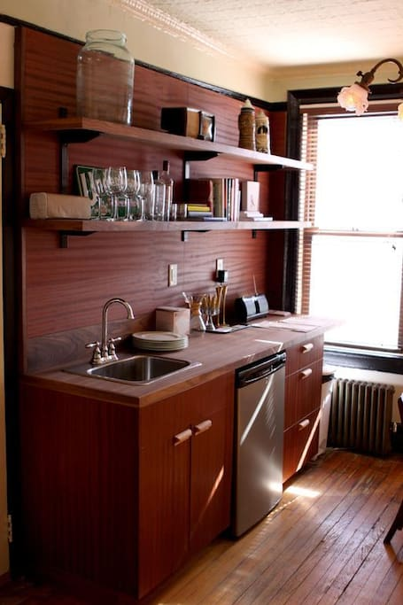 Cozy kitchenette with dining table, sink, small fridge with Chemex coffee maker.