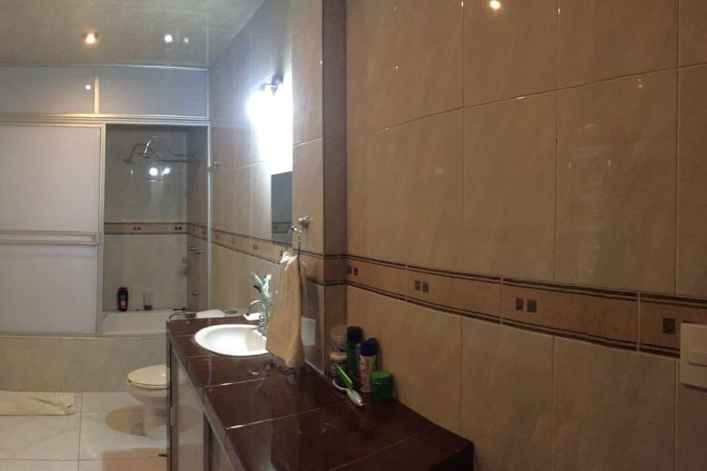 Vista del amplio cuarto de baño con regadera integrada en la tina de baño sencilla, agua caliente.