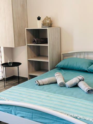 Комната с двухспальной кроватью и раскладным креслом.