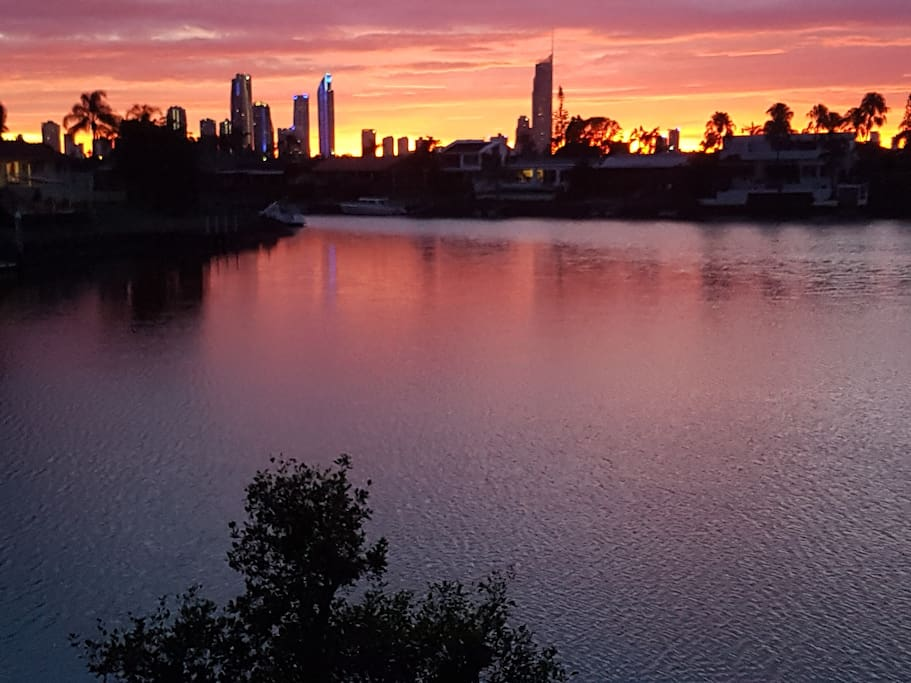 Looking at silhouette of Surfers Paradise at night from back garden. Sunbeds provided down by the water's edge.