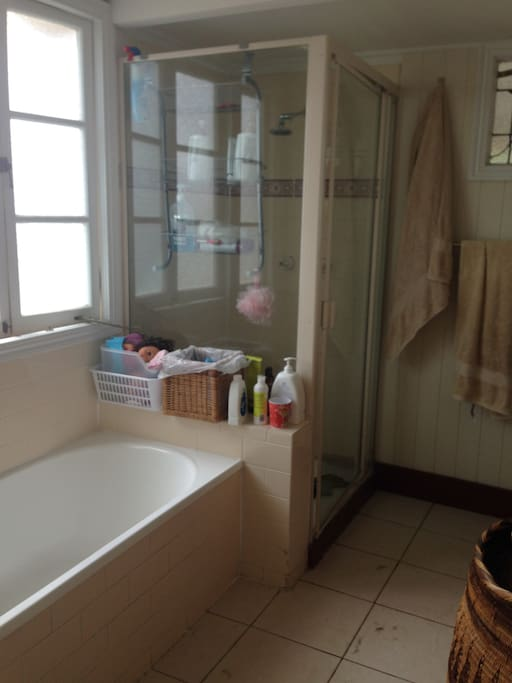Shared bathroom with bath tub and shower