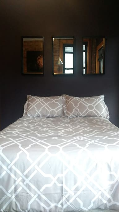 The bed has a down comforter with duvet cover and 4 pillows. The mattress is a full size pillow top on a box spring. It is in a soft (it makes no crinkly noise) fully protective waterproof case with mattress pad and high thread count cotton sheets on top. Mattress pad, sheets and duvet cover are washed between every guest.