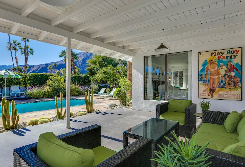 The outdoor living area is shaded with private views of the pool and mountains.