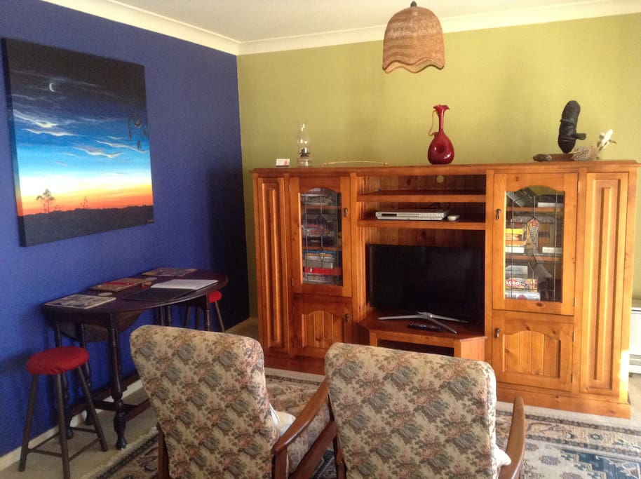 small sitting room with TV, board games and sitting table.
