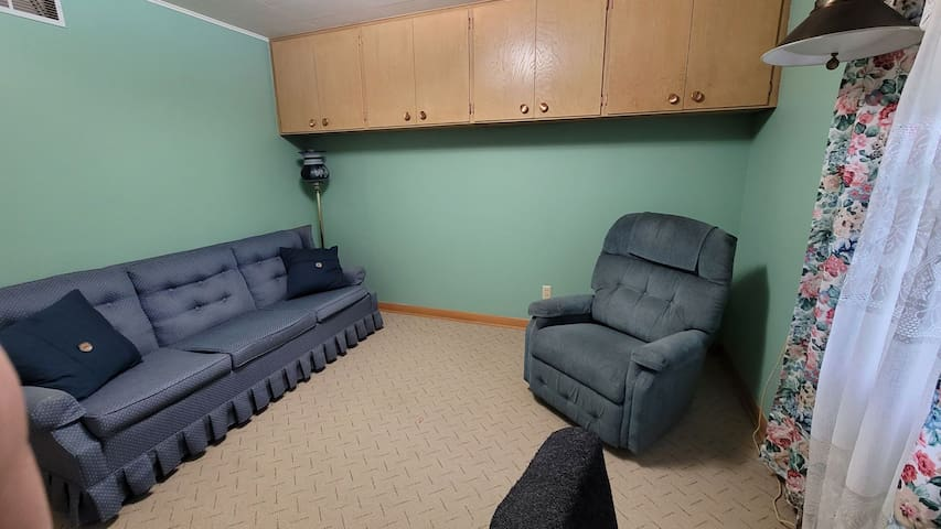 Sitting room with a sofa to sleep on and a desk.
