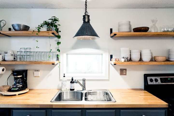 Stainless kitchen sink with overhead lighting and open shelving.