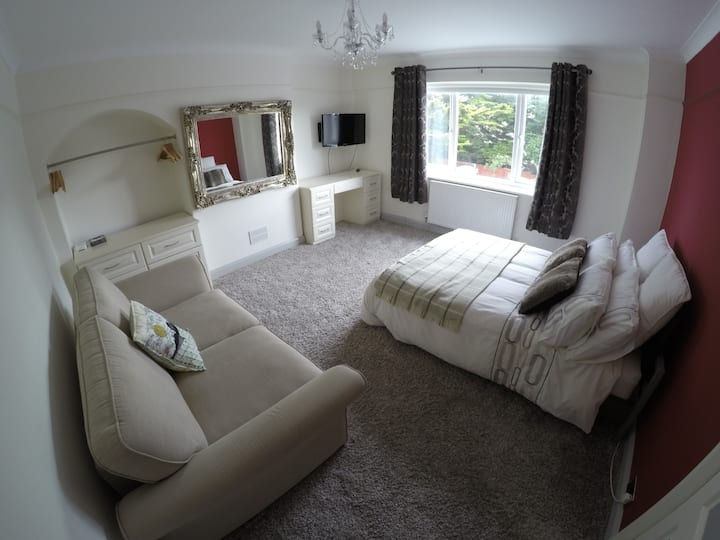 Spacious room with sofa and desk in Goring