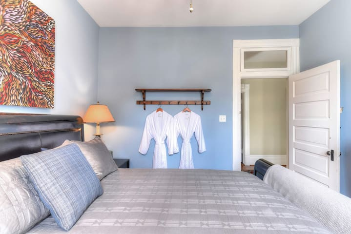 Blue Room Equipped with spa robes in 2 different sizes, attached hanging rack pictured.