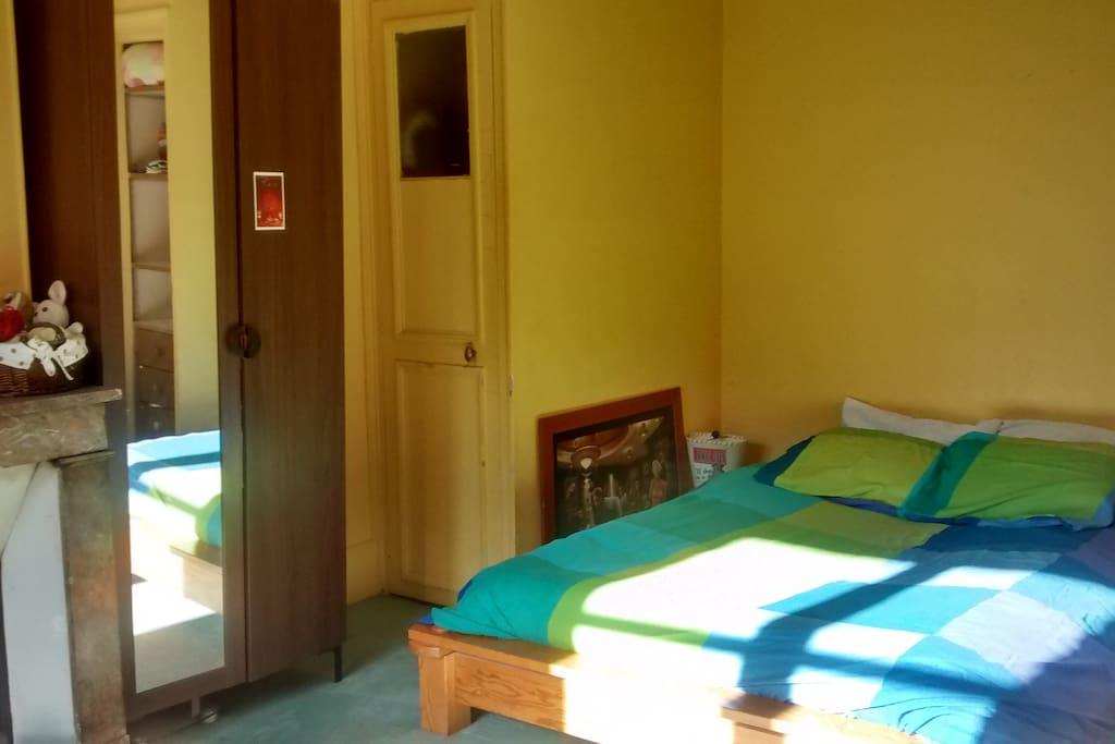Une chambre spacieuse et lumineuse, avec un lit double confortable, un placard et une penderie à disposition des invités.