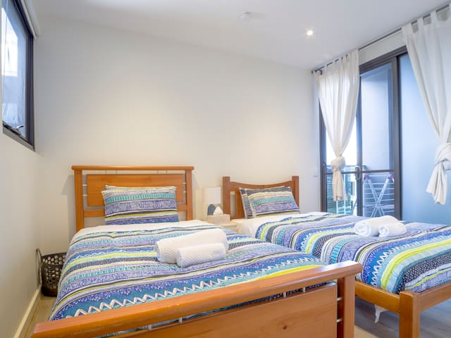Secondary Bedroom with access to Secondary Balcony, Two King Single Beds & Built-in Wardrobe