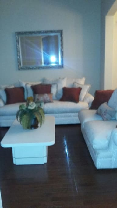 1 of 2 large living spaces. Wood floors, comfortable furniture. Cable/satellite televisions in living spaces and bedroom