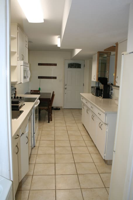 Galley kitchen is fully stocked with plates, cups, pots, pans, small appliances, etc.