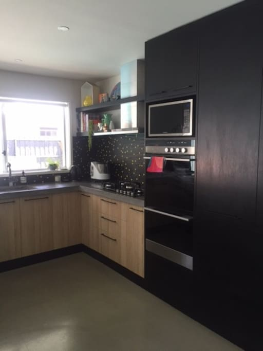 Large and well equipped kitchen with double ovens, gas cook top and microwave, concrete bench tops