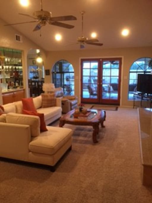 """Living Room with wetbar, 55"""" Smart TV, Gas fireplace, direct access through french doors to covered patio"""