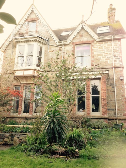 The house! 2 minutes walk to the sea Penzance Bay. 6 person Hot tub in a garden that feels private due to tall mature trees. Trampoline 14 ft diameter, barbecue area, patio, conservatory, pretty Victorian porch, secret wooden hut with log burner.
