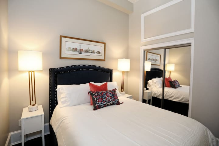 Master Bedroom, Queen Bed, with built in storage in the frame below.  Reading lamps and high-end bedding.