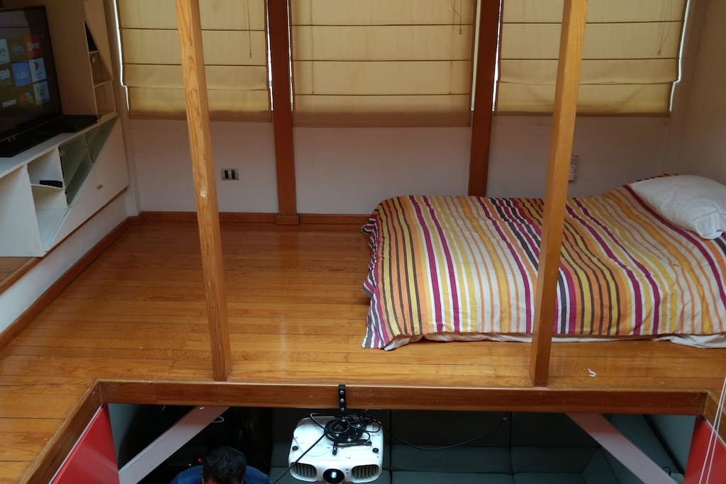 Room with double bed, television and living room