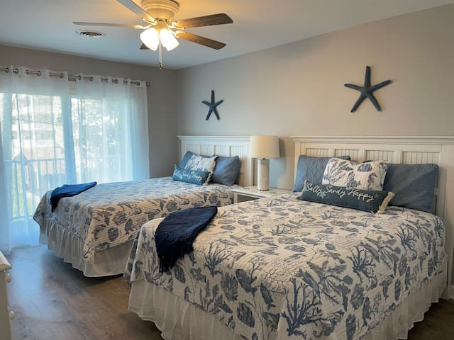 Spacious second bedroom has two queen-size beds; access to balcony