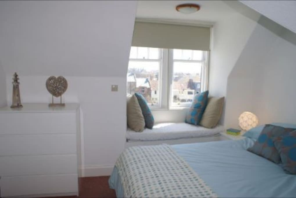 Beautiful bright airy bedroom with view out over harbour