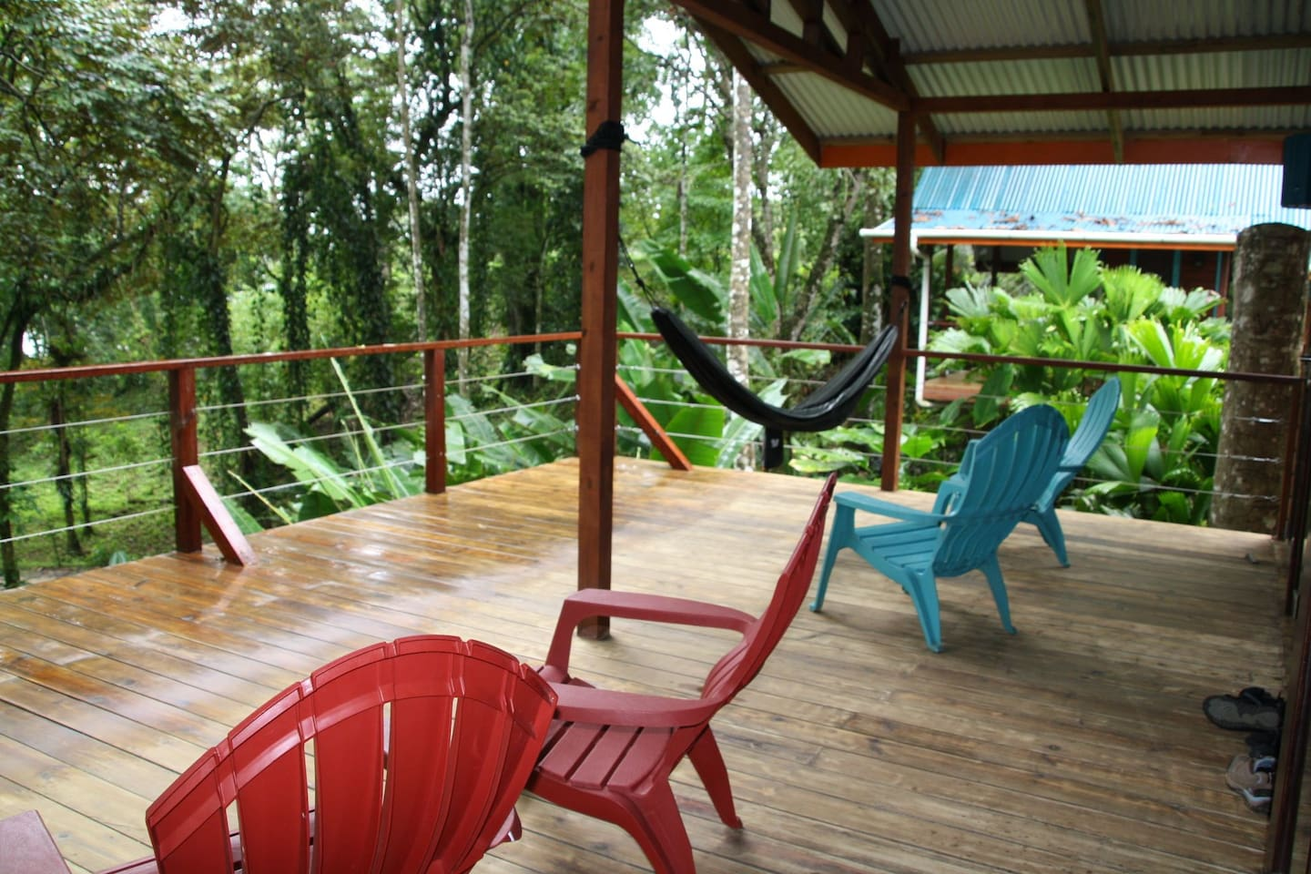 View of the jungle from your private deck with lounge chairs and hammock