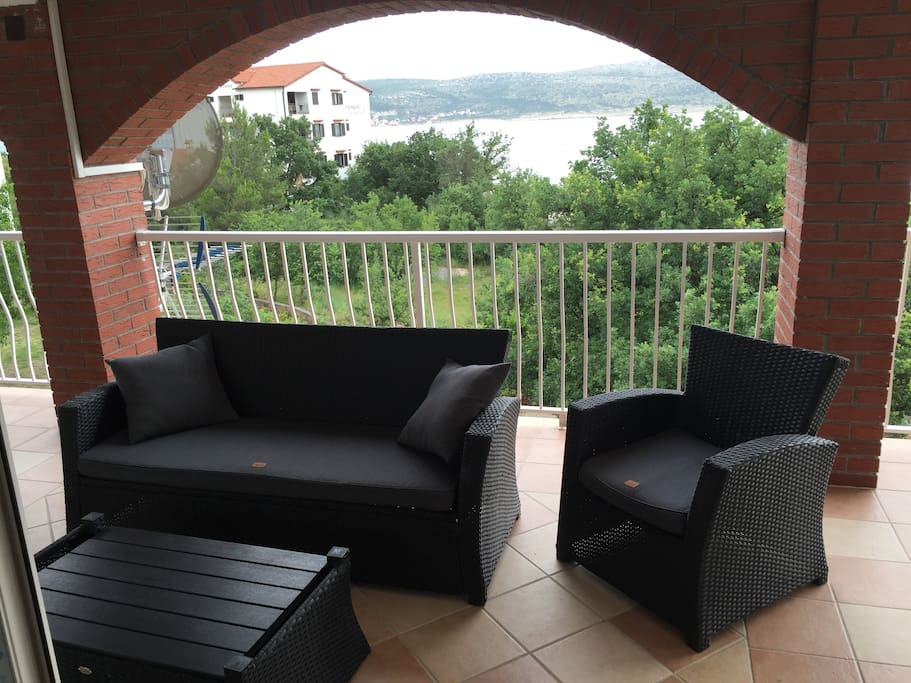 Covered terrace with patio furniture, perfect for escaping the heat or relaxing in the evening