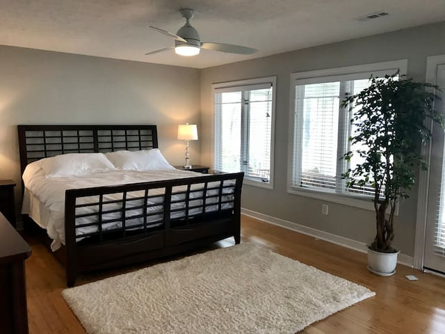 Main bedroom - spacious room with beautiful river views. King bed, 2 end tables w/ lamps, large dresser, TV armoire, and chair. Double doors from the hallway, and pocket door to the the fitness room. Ceiling fan and direct access to the porch.
