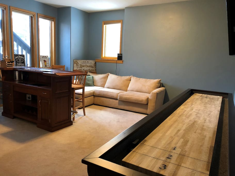 """Basement - including full oak bar, 55"""" TV, and a brand new shuffleboard to keep everyone entertained"""