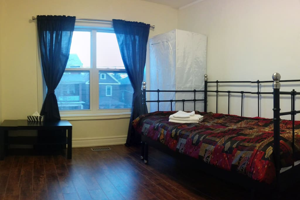 the room with bed, closet, coffee table, full length mirror, towels, garbage bin, notepad and pen
