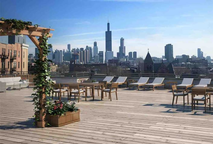 Massive roof deck with skyline views and luxury outdoor furniture.