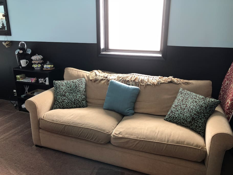 Comfy couch next to Keurig and snack stand