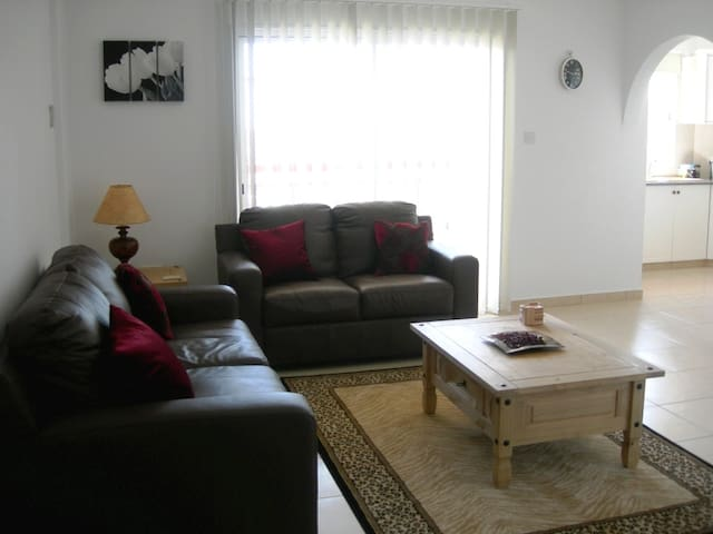 Comfortable air conditioned living room leading to separate kitchen and dining area