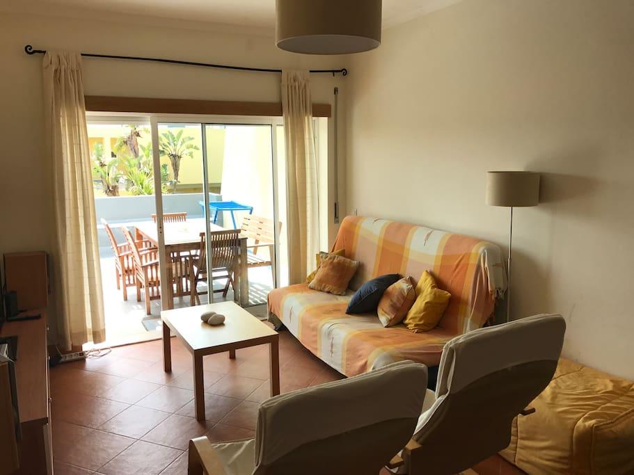 Vista geral da sala de estar com acesso à varanda e vista para a piscina, mini golf e parque infantil