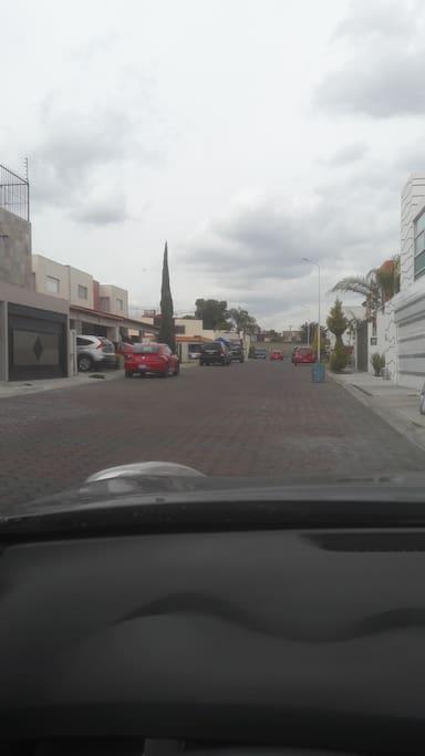 """Vista desde la calle...  """"Mi casa tu casa """" justo donde esta estacionado el vehiculo rojo... Se puede observar la tranquilidad del fraccionamiento."""