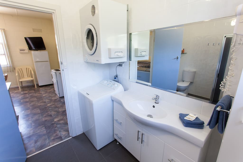 Large renovated bathroom with washer and dryer