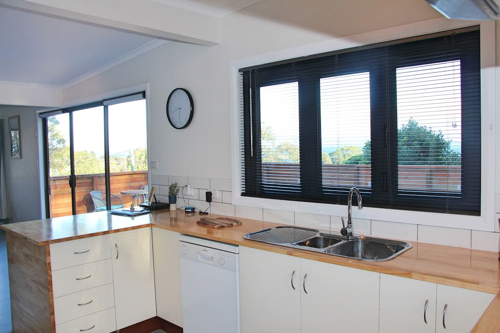 Kitchen that looks out onto deck and over the ocean towards Hobart.