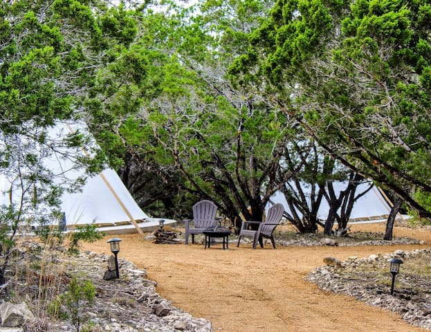 On left is El Sol tipi and in the background Is La Luna tipi. La luna tipi has two brown outdoor lounging chairs like the ones pictured.