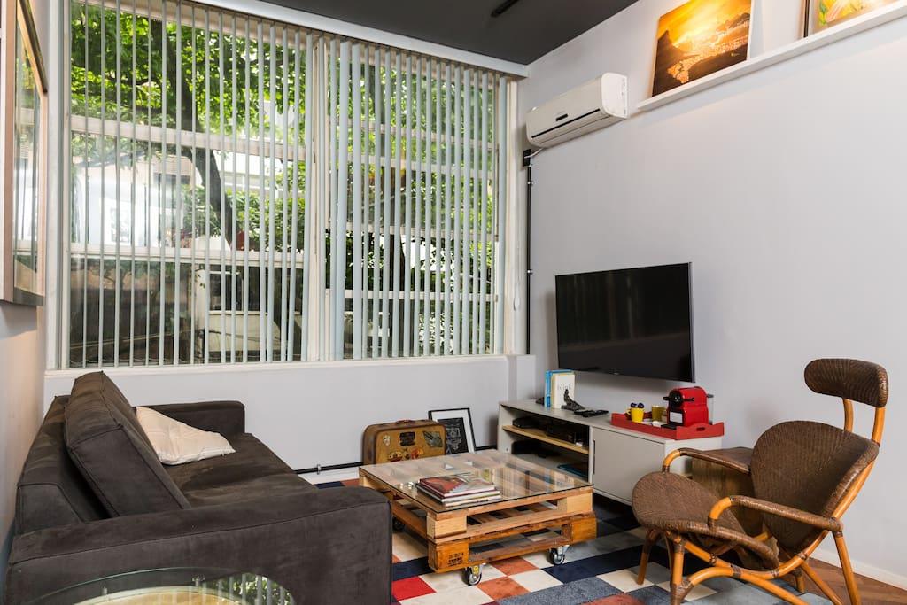 Sala do apartamento.  Sofá e poltrona.  TV com NET HD.